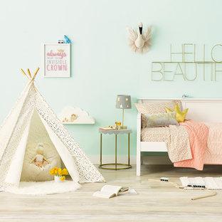 Réalisation d'une chambre d'enfant de 4 à 10 ans minimaliste de taille moyenne avec un mur bleu, un sol en bois clair et un sol beige.
