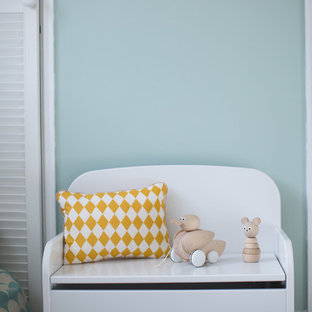 Photo of a small scandinavian toddler's room for girls in Surrey with green walls, carpet and grey floors.