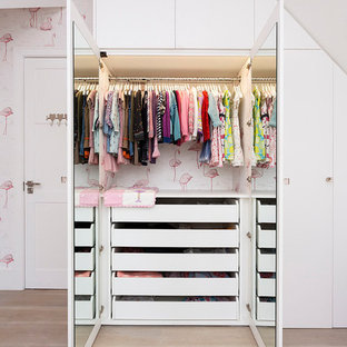 Photo of a contemporary kids' bedroom for girls in London with light hardwood flooring.