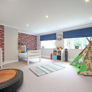 Immagine di una grande cameretta per bambini da 4 a 10 anni design con pareti grigie e moquette