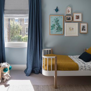 This is an example of a small contemporary gender neutral children's room in London with blue walls, carpet and grey floors.
