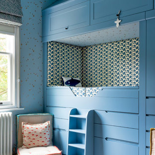 Photo of a classic gender neutral children's room in London with blue walls, carpet and beige floors.