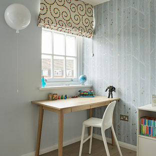 Small contemporary gender neutral children's room in London with multi-coloured walls, light hardwood flooring and beige floors.
