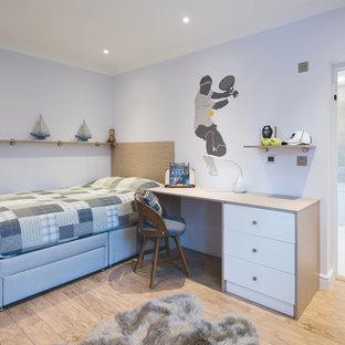 Inredning av ett modernt mellanstort pojkrum kombinerat med sovrum och för 4-10-åringar, med vita väggar, laminatgolv och beiget golv