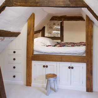 Farmhouse gender-neutral carpeted kids' bedroom photo in Sussex with white walls