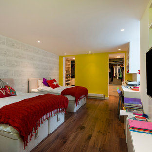 Contemporary gender neutral children's room in London with dark hardwood flooring and yellow walls.