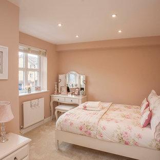 Inredning av ett klassiskt mellanstort flickrum, med rosa väggar, heltäckningsmatta och beiget golv