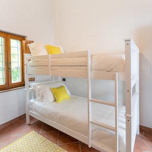 Esempio di una piccola cameretta per bambini country con pareti bianche, pavimento in terracotta e pavimento arancione