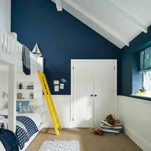 Aménagement d'une chambre d'enfant de 4 à 10 ans bord de mer avec un mur bleu, moquette, un sol marron, un plafond en lambris de bois, un plafond voûté et boiseries.
