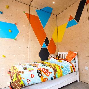 Inredning av ett skandinaviskt mellanstort pojkrum kombinerat med sovrum och för 4-10-åringar, med flerfärgade väggar och betonggolv