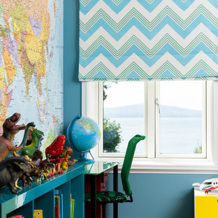 This is an example of a medium sized contemporary kids' study space for boys with blue walls, light hardwood flooring and beige floors.