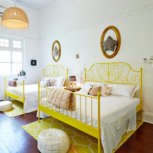 Photo of a world-inspired kids' bedroom with white walls, medium hardwood flooring and brown floors.
