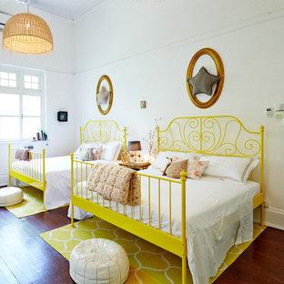 Idée de décoration pour une chambre d'enfant ethnique avec un mur blanc, un sol en bois brun et un sol marron.
