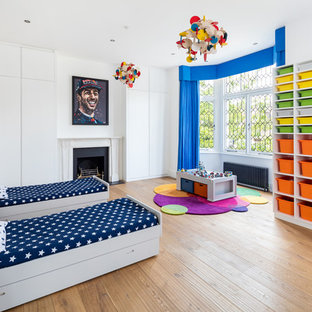 Inspiration for a large contemporary children's room in London with white walls, light hardwood flooring and beige floors.