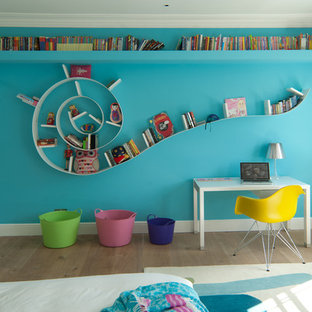 This is an example of a contemporary gender neutral children's room in Kent with medium hardwood flooring and multi-coloured walls.