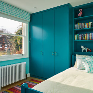 Inspiration for a small contemporary children's room for girls in Surrey with blue walls, light hardwood flooring and brown floors.