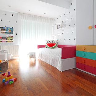 Modelo de dormitorio infantil de 1 a 3 años, actual, de tamaño medio, con paredes blancas, suelo laminado y suelo marrón