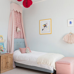 This is an example of a traditional children's room for girls in Edinburgh with blue walls, carpet and beige floors.