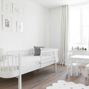 Example of a large danish girl kids' room design in London with white walls