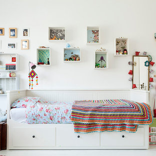 This is an example of a classic children's room for girls in London with white walls, painted wood flooring and white floors.