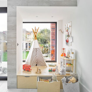 This is an example of a scandinavian gender neutral kids' bedroom in London with white walls and grey floors.