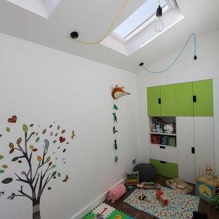 Diseño de dormitorio infantil de 1 a 3 años, moderno, de tamaño medio, con paredes blancas y suelo de madera oscura