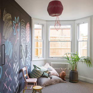 Bohemian children's room for girls in London with carpet and multi-coloured floors.