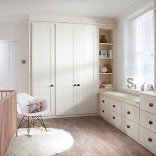 Design ideas for a traditional toddler's room in West Midlands with white walls and medium hardwood flooring.