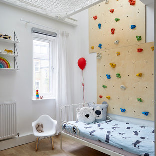 Small scandi kids' bedroom in London with multi-coloured walls and light hardwood flooring.