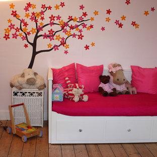 Modelo de dormitorio infantil de 1 a 3 años, minimalista, de tamaño medio, con paredes rosas y suelo de madera en tonos medios