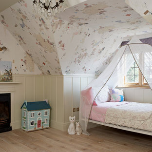 Inspiration for a traditional kids' bedroom for girls in London with multi-coloured walls and light hardwood floors.