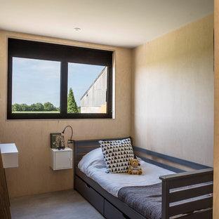 Esempio di una piccola cameretta per bambini da 4 a 10 anni scandinava con pareti beige, pavimento in cemento e pavimento grigio