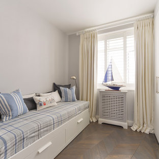 Design ideas for a small beach style kids' bedroom for kids 4-10 years old and boys in London with grey walls, dark hardwood floors and brown floor.