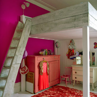 This is an example of a vintage kids' room for girls in London with pink walls and painted wood flooring.