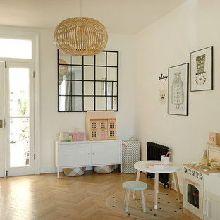Photo of a medium sized scandinavian children's room for girls in Surrey with white walls, light hardwood flooring and beige floors.