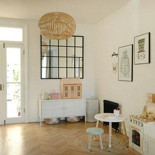Esempio di una cameretta per bambini da 4 a 10 anni scandinava di medie dimensioni con pareti bianche, parquet chiaro e pavimento beige