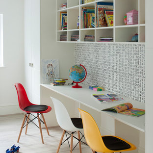 Inspiration for a contemporary gender neutral kids' study space in London with white walls and light hardwood flooring.