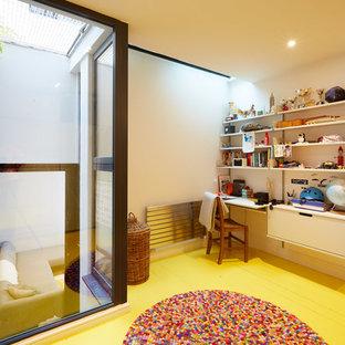 Inspiration för mellanstora moderna könsneutrala barnrum, med målat trägolv och gult golv
