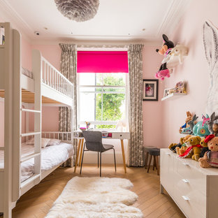 Photo of a traditional children's room for girls in London with pink walls, light hardwood flooring and beige floors.