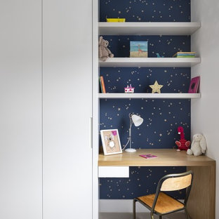 This is an example of a small contemporary kids' study room for kids 4-10 years old and girls in London with blue walls, carpet and grey floor.