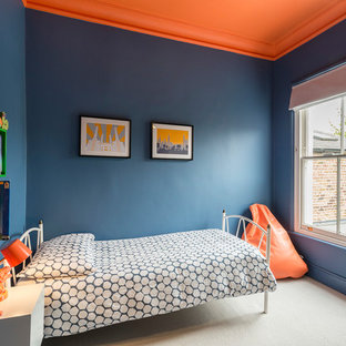 Design ideas for a contemporary kids' room for boys in London with blue walls, carpet and beige floors.