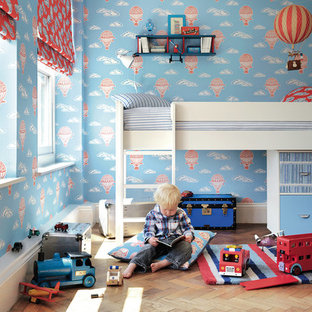 Traditional kids' room for boys in London with blue walls, medium hardwood flooring and brown floors.