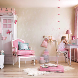 Design ideas for a traditional kids' room for girls in London with multi-coloured walls, light hardwood flooring and beige floors.