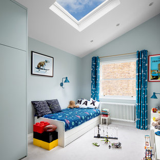 This is an example of a contemporary kids' bedroom in London with blue walls, carpet and grey floors.