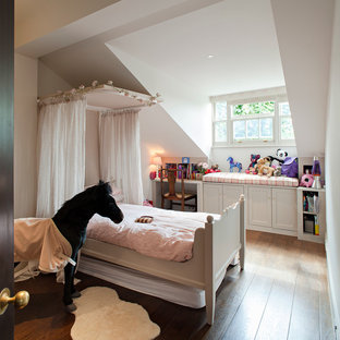 Example of a small classic girl medium tone wood floor kids' room design in London with white walls