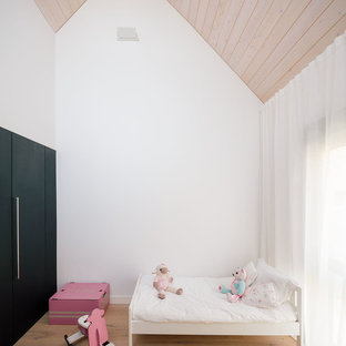 Photo of a mid-sized contemporary kids' bedroom for kids 4-10 years old and girls in Madrid with white walls, medium hardwood floors and brown floor.