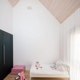 Imagen de dormitorio infantil de 4 a 10 años, actual, de tamaño medio, con paredes blancas, suelo de madera en tonos medios y suelo marrón