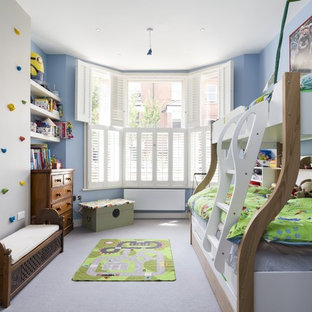 Medium sized bohemian children's room for boys in London with blue walls, carpet and grey floors.
