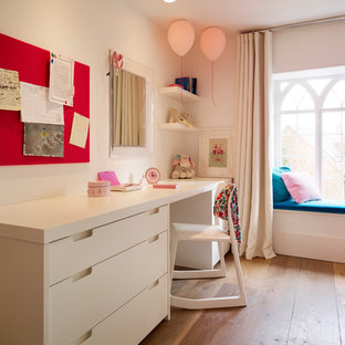 Photo of a contemporary kids' room for girls in Oxfordshire with medium hardwood flooring.