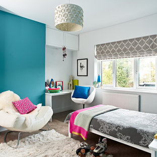 This is an example of a large contemporary teen's room for girls in Berkshire with blue walls, carpet and grey floors.